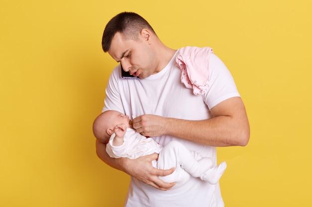 Jovem pai europeu ocupado com uma conversa ao telefone, posando com seu bebê recém-nascido