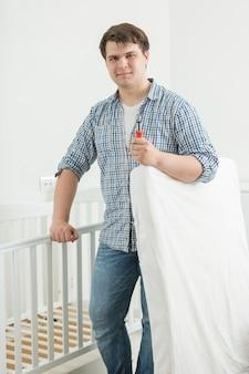 Jovem pai expectante colocando colchão no berço