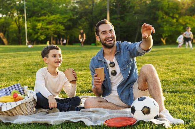 Jovem pai feliz fazendo um piquenique com seu filho pequeno no parque, bebendo de um copo