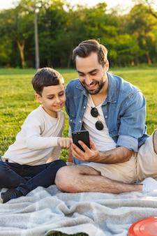 Jovem pai feliz fazendo um piquenique com seu filho pequeno no parque, olhando para o celular