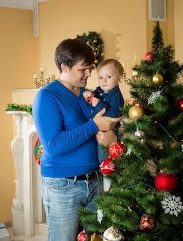 Jovem pai feliz segurando seu filho bebê e olhando para a árvore de natal