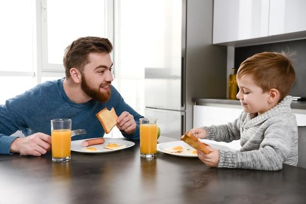 Jovem pai feliz vestido de suéter azul comendo na cozinha com seu filho pequeno
