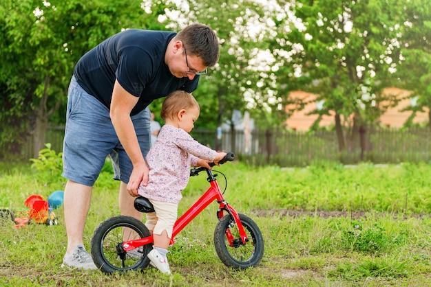 Jovem, pai, gastar tempo, com, cute, pequeno, um, anos velho, toddler, criança menina, e, equilíbrio, bicicleta