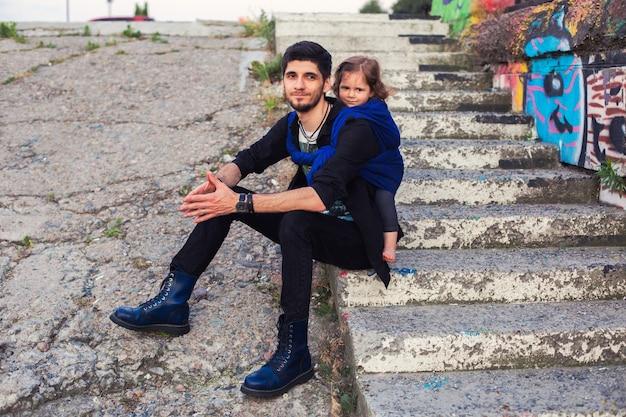 Jovem pai hippie com uma menina em um estilingue azul em meio urbano.