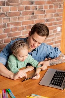 Jovem pai hipster de conteúdo com tatuagem no braço, sentado à mesa com dispositivos e canetas hidrográficas multicoloridas e jogando para celular com a filha