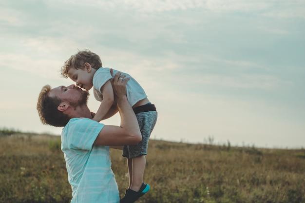 Jovem pai joga seu filho fofo e pequeno para o ar fresco. dia dos pais, pai e filho menino brincando e se abraçando ao ar livre.