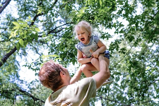 Jovem pai levanta sua filhinha alegre bem alto com as mãos contra o céu e árvores verdes