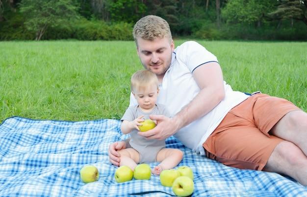 Jovem pai loiro caucasiano bonito dando maçã verde ao bebê sentado na manta no parque, no piquenique no verão. alimentos saudáveis, frutas para o conceito de crianças