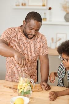 Jovem pai misturando fatias de limão e folhas de hortelã cortadas em uma jarra