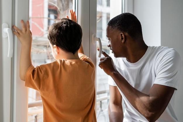 Jovem pai mostrando algo para o filho na janela