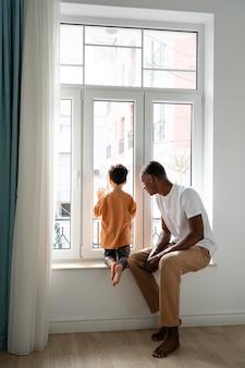 Jovem pai olhando pela janela com o filho
