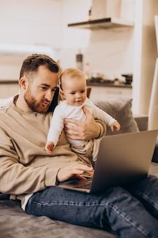 Jovem pai sentado com sua filha e usando o computador em casa