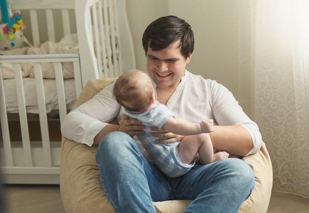 Jovem pai sentado em uma cadeira de pufe e segurando seu filhinho.
