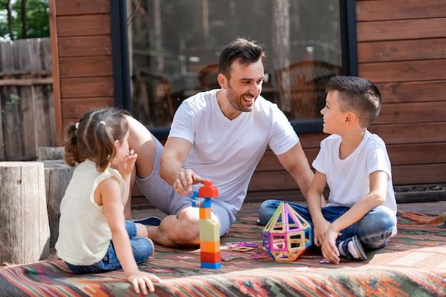 Jovem pai sorri e se comunica com seus filhos pequenos, passa os fins de semana de verão brincando com seu filho e filha