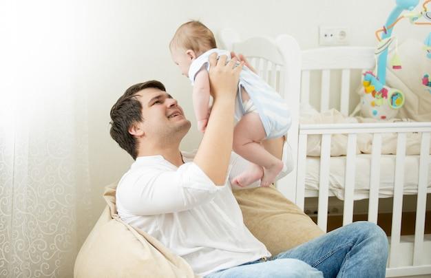 Jovem pai sorridente brincando com seu filho de 6 meses no quarto