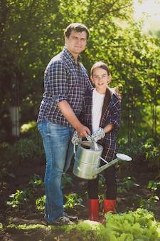 Jovem pai sorridente regando o jardim com a filha pequena