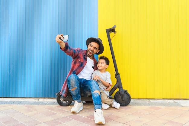 Jovem pai tomando um selfie com seu filho em uma scooter elétrica.