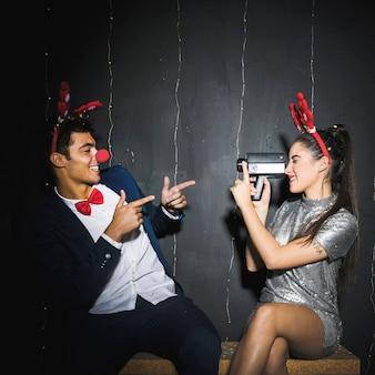 Jovem, par, com, veado, antlers, headbands, e, engraçado, narizes, capturar, ligado, vídeo