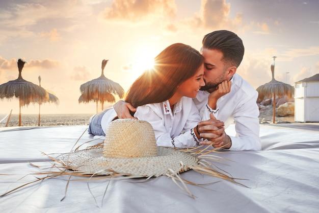 Jovem, par, praia, lounge, pôr do sol