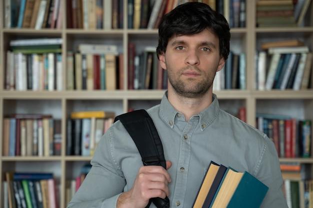Jovem parado com livros e uma mochila na biblioteca