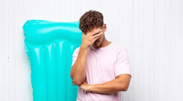Jovem parecendo estressado, envergonhado ou chateado, com dor de cabeça, cobrindo o rosto com a mão. conceito de férias