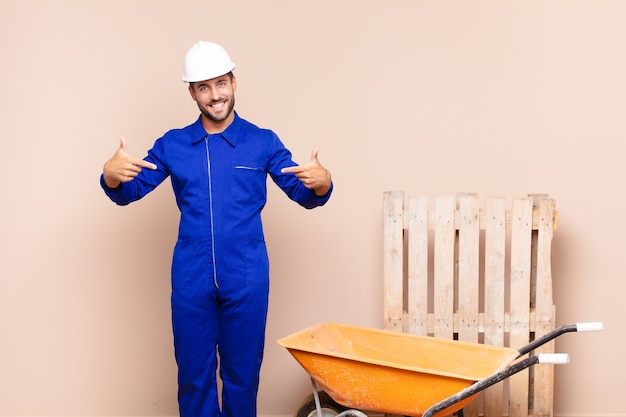 Jovem parecendo orgulhoso, arrogante, feliz, surpreso e satisfeito, apontando para si mesmo, sentindo-se um conceito de construção vencedor