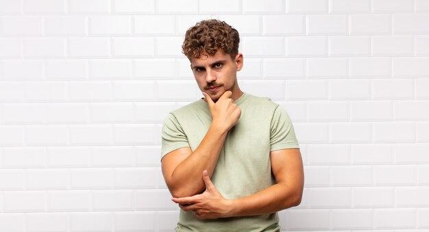 Jovem parecendo sério, confuso, incerto e pensativo, duvidando entre opções ou escolhas