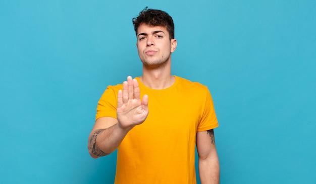 Jovem parecendo sério, severo, descontente e irritado, mostrando a palma da mão aberta fazendo gesto de pare