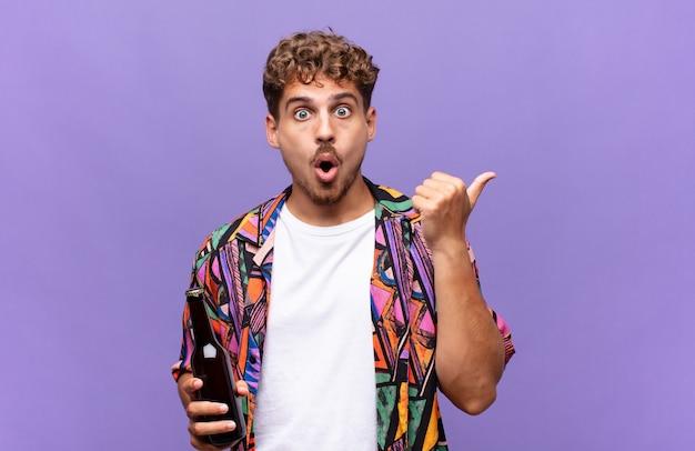 Jovem parecendo surpreso em descrença, apontando para o objeto ao lado e dizendo uau, inacreditável. conceito de férias