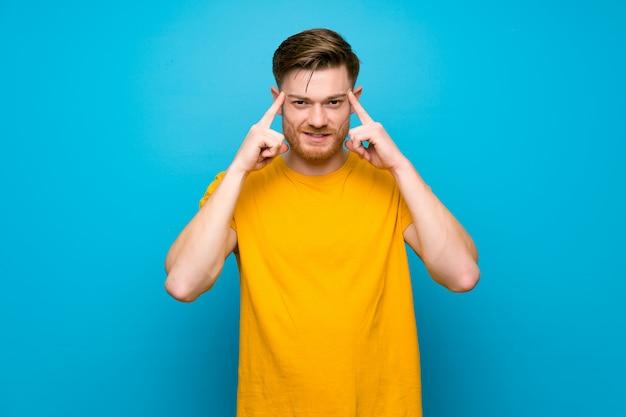Jovem, parede azul, mostrando sinal de ok e dando um polegar para cima gesto