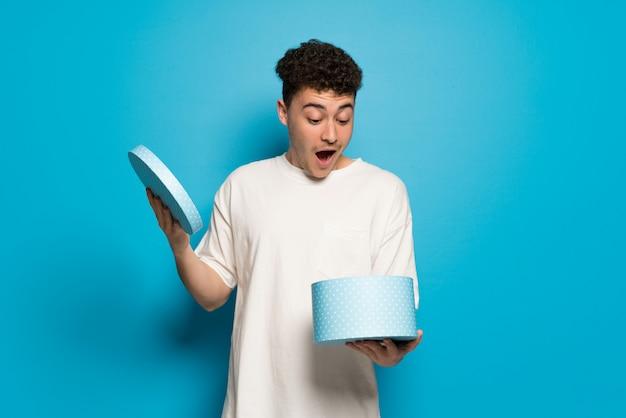 Jovem parede azul segurando um presente nas mãos