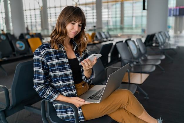 Jovem passageira do aeroporto com telefone inteligente e laptop sentada na sala do terminal enquanto espera seu voo