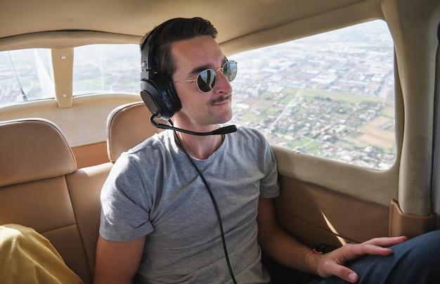 Jovem passageiro do sexo masculino sorridente sobrevoando a cidade em uma aeronave