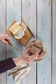 Jovem passando manteiga em um pão em uma velha mesa rústica.