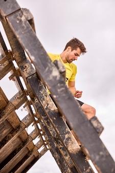 Jovem passando por uma pista de obstáculos em uma corrida espartana