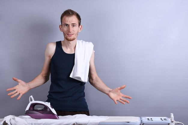 Jovem passando roupa na tábua de passar roupa