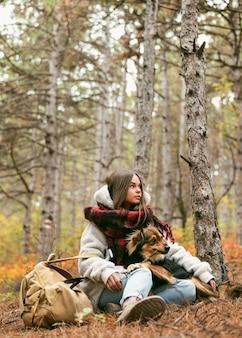 Jovem passando um tempo junto com seu cachorro do lado de fora