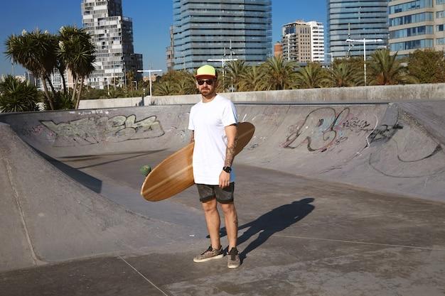 Jovem patinador tatuado e atraente com boné de caminhoneiro em t-shitrt branco sem rótulo com seu longboard de madeira na mão no centro do skatepark, paisagem urbana atrás
