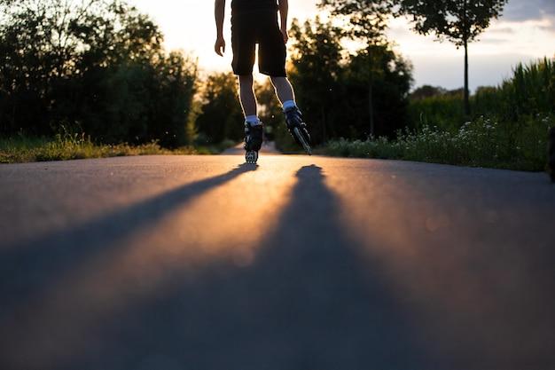 Jovem, patinando na ciclovia durante o lindo pôr do sol de verão
