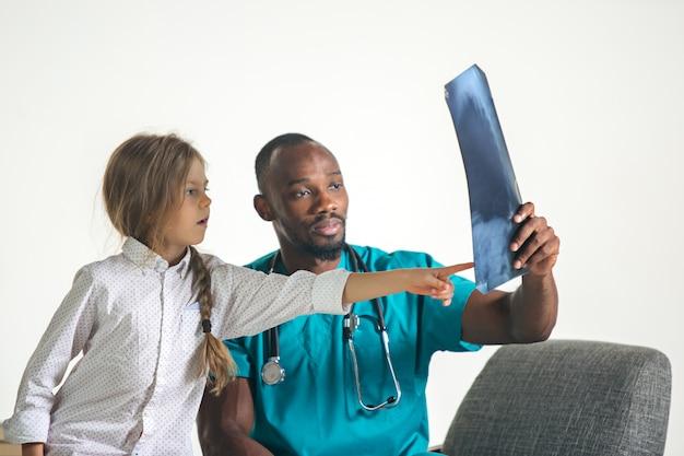 Jovem pediatra masculino africano, explicando o raio-x para criança