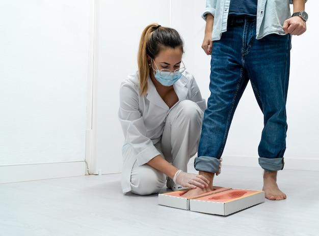Jovem pedicuro mascarado examinando os pés de um paciente na espuma para palmilhas