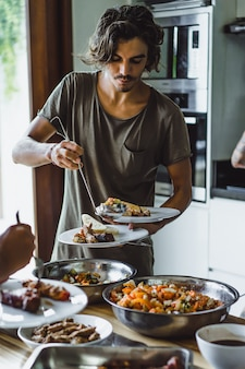 Jovem pega comida em um prato em uma festa