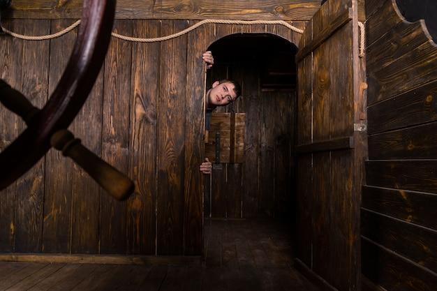 Jovem pendurado na moldura da porta e espiando por dentro da porta da cabine de um antigo navio à vela de madeira