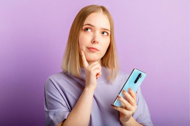 Jovem pensa a dúvida sobre a pergunta usando o smartphone. menina adolescente curiosa sonhando, escolher ou decidir olhar do lado no espaço da cópia. retrato de emoção isolado sobre a parede de cor roxa.