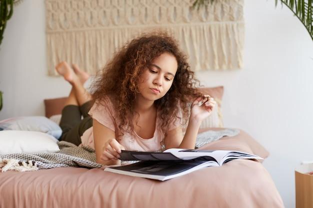 Jovem pensativa afro-americana com cabelos cacheados, deita-se na cama, lê um artigo em uma revista de forma concentrada.