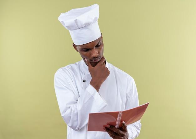 Jovem pensativa afro-americana com uniforme de chef olha para um caderno isolado na parede verde