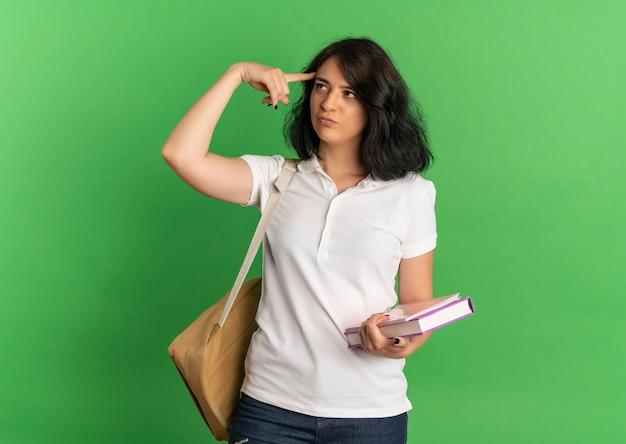 Jovem pensativa, bonita e caucasiana colegial vestindo uma bolsa traseira coloca o dedo na cabeça segurando livros em verde com espaço de cópia