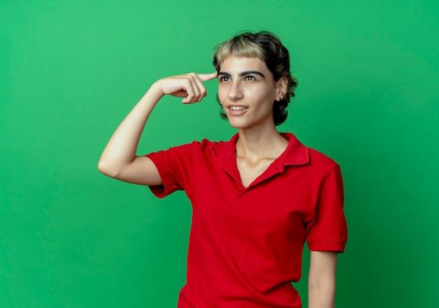 Jovem pensativa caucasiana com corte de cabelo de duende olhando direto com o dedo na têmpora isolada em um fundo verde com espaço de cópia