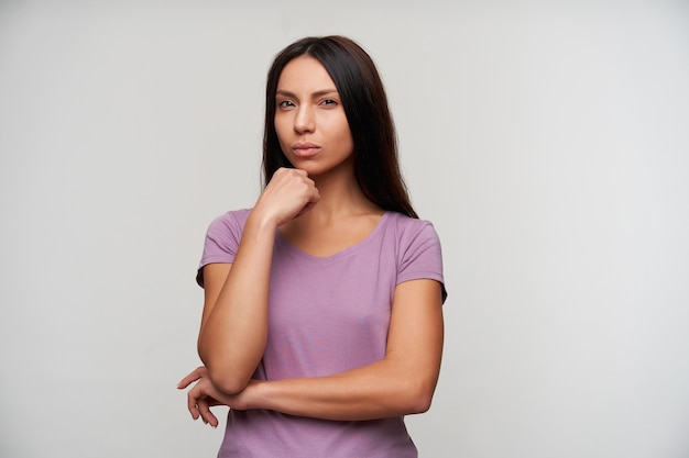 Jovem pensativa com cabelos muito escuros e maquiagem natural, apoiando o queixo na mão levantada enquanto posa em branco, apertando os olhos enquanto olha pensativamente