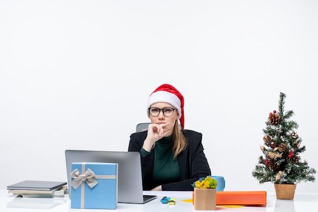 Jovem pensativa com chapéu de papai noel, sentada à mesa com uma árvore de natal e um presente, apontando para cima, no fundo branco